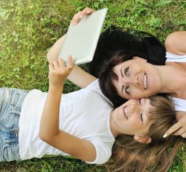 lifestyle family portrait of happy girl and her mother having fun on the grass in sunny summer day happy lifestyle family concept lifestyle concept